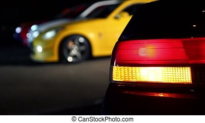 Automobile taillight blinks at background of several cars