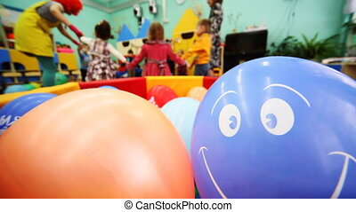 inflatable ball is smiling, in defocus behind it children playing with clown and caregiver