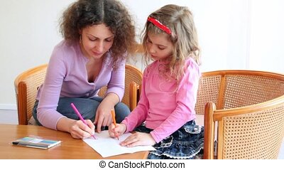 Mother with her daughter sit on chairs at wooden table and draw with markers