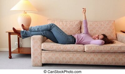 Young woman lies on sofa and dances at room with lamps on each side