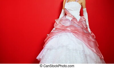 beautiful bride rotates showing wedding dress on red...
