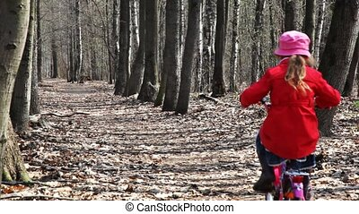 sister and brother go away on bicycles at park in spring