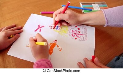 Woman and little girl draw princess on paper with colored markers