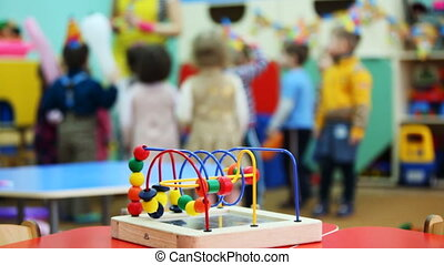 conundrum toy standing on table, in defocus behind it children play