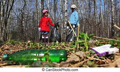 brother and sister with bags collect trash in park - brother...