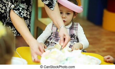 child-minder lays out pieces of cake to kids sitting at...