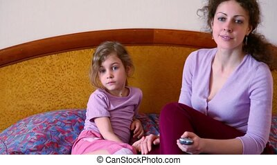 Mother and her little daughter sit on bed and watch tv,...