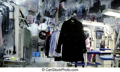 Machine work among lot of clothes in dry cleaning, few women...
