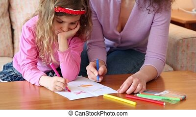 Mother with daughter sit on sofa at wooden table and draw with markers