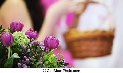 beautiful bouquet flowers in back and defocus girl holding basket of twigs