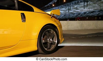 Yellow sport car stand at background of bridge at night,...