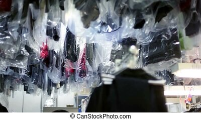 Many clothes hang and move in dry cleaning