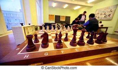Chess starting position on board closeup, people play at...