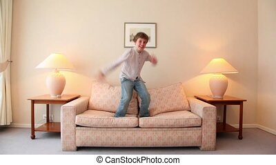 Little boy jumps on sofa at room with lamps on each side