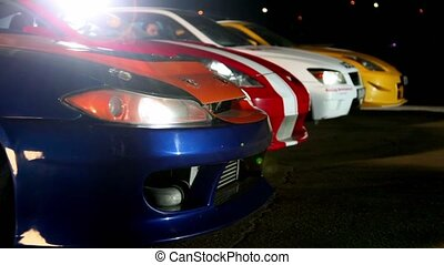 Four cars with colorful sport design at night