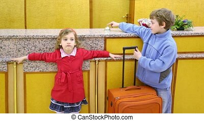 Two kids boy with girl stand with trunk at hotel reception...