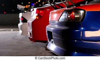 Three cars with colorful sport design at night, only bumpers...
