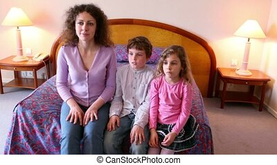 Mother and her kids boy and girl sit on sofa and clap hands when watch tv