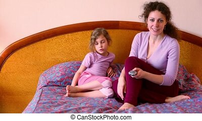 Mother and daughter sit on bed and watch tv with remote...