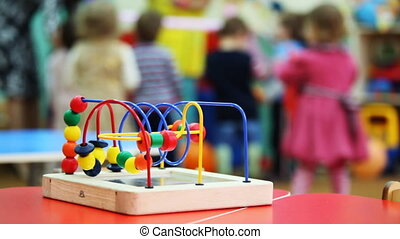 close-up conundrum toy standing on table, in defocus behind it children play