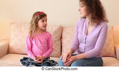 Little girl sits on sofa with her mother and tells her about...