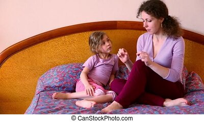 Mother sits on bed with her little daughter and tells her about something
