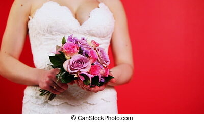 bride in white dress holding bouquet of roses on red...