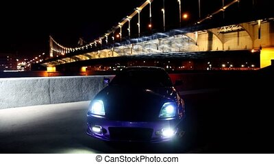 Car stand with parking lights blinks at background of bridge