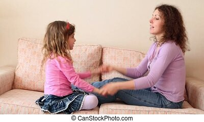 Mother and her little daughter sit on sofa and play hands...