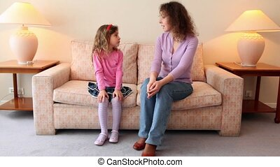 Mother sits on sofa with her little daughter and tells her about something