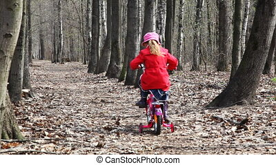 little girl goes away on bicycle at park in spring