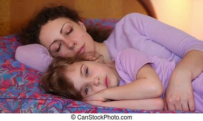 Mother and daughter sleep on bed, then they wakes and mom kiss girl