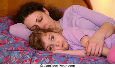 Mother with her little daughter lay on bed, mom sleeps but girl makes faces