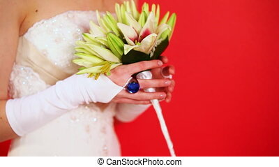 bride in white dress holding bouquet of lilies on red...