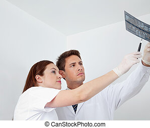 Doctor And Assistant Analyzing Patient's Report