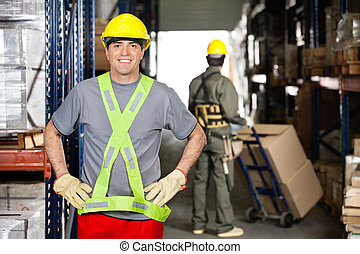 Mid Adult Foreman With Hands On Hips At Warehouse - Portrait...