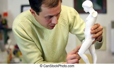 Sculptor polishes female figurine legs by file and look on it