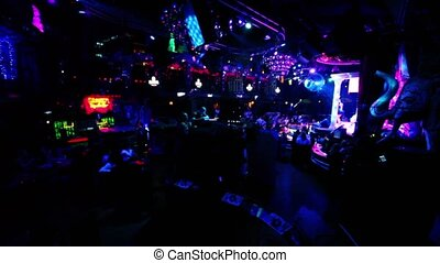 Many people in dark night club with colorful illumination