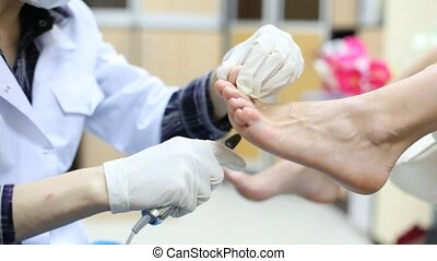 Beautician in rubber gloves grinds woman foot on doing...