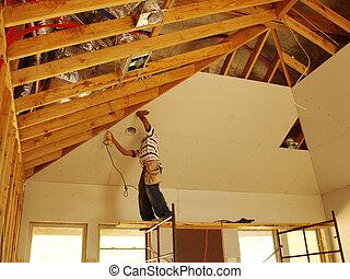 Sheetrocking on a scaffol - Worker putting up sheetrock on a...