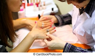 Cosmetician has made to client of manicure and has made up nails pink nail polish