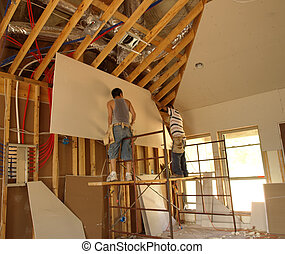 Working together to put up a sheet of sheetrock