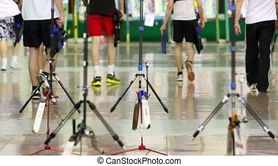 Several young sportsmens archers walk away in shooting gallery