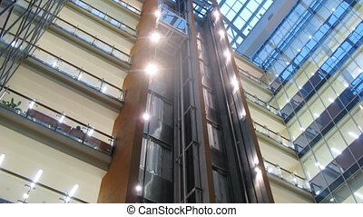 Two lifts move downwards and upwards in business center,...