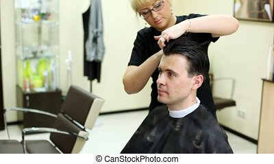 Hairdresser cuts hair to man with long hair by scissors -...