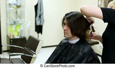 Young man sits in hairdressing salon in seat to make...