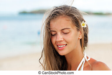 happy beautiful young woman smiling on tropical beach