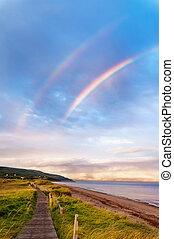Sunrise at a beach with double rainbow