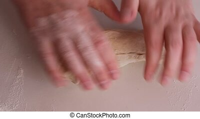 female hands in flour closeup kneading dough on table