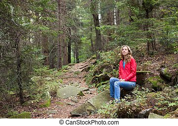 Hiker woman sitting on a halt in stones among the forest